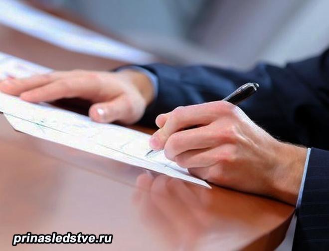 Человек пишет ручкой на бумаге