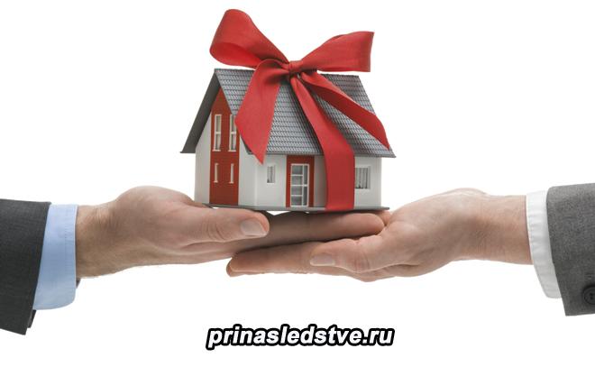 Человек дарит другому человеку игрушечный домик
