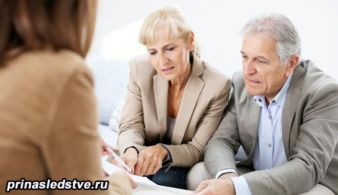 Пожилая пара общается с женщиной