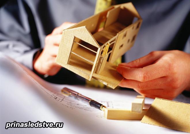 Мужчина разбирает деревянный игрушечный домик