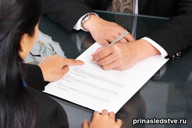 Мужчина заполняет бумагу, женщина объясняет ему как заполнять