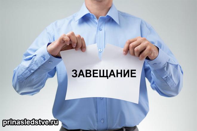 Человек рвет бумагу с надписью завещание