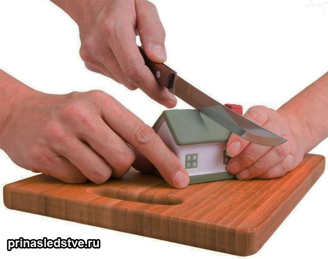 На разделочной доске разрезают ножом игрушечный домик