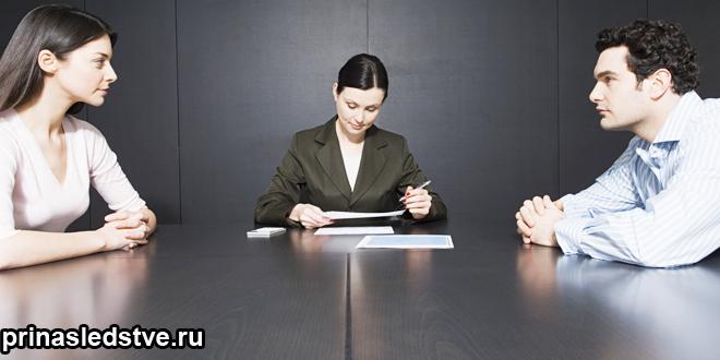 Женщина и мужчина сидят напротив друг друга за столом, между ними сидит женщина и читает бумагу