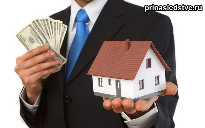 Мужчина в костюме держит деньги и игрушечный домик