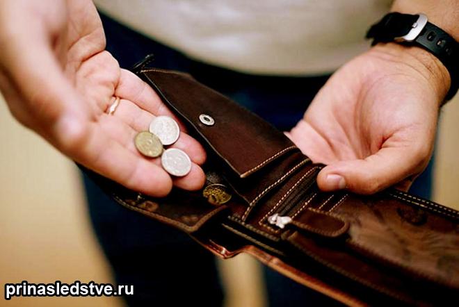 Мужчина достает из кошелька монеты