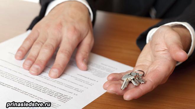 Человек читает бумагу и в руке держит ключ от дома