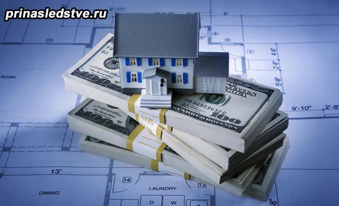 Игрушечный домик стоит на пачке денег и плане квартиры
