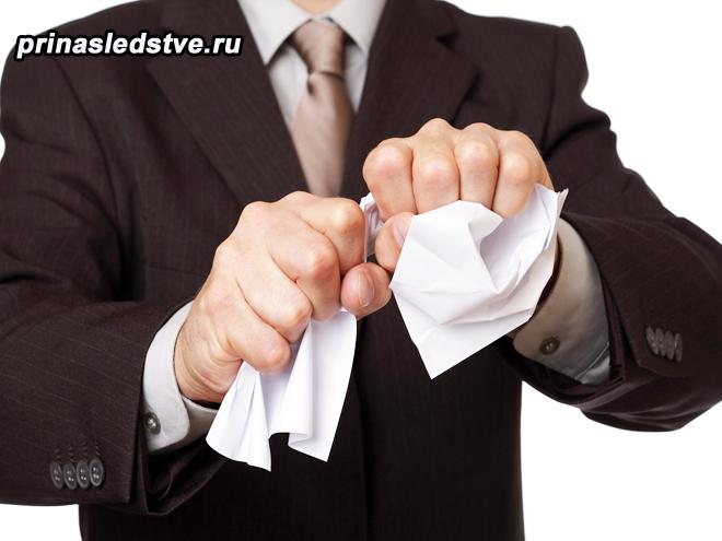 Мужчина в костюме комкает бумагу