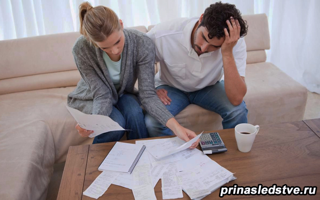 Мужчина и женщина изучают бумаги, сидя на диване