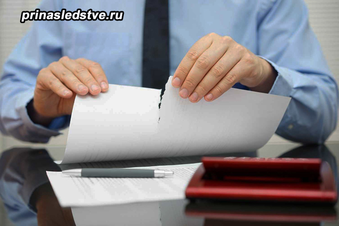 Мужчина разрывает бумагу на пополам