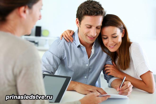 Молодая пара подписывает бумаги, рядом женщина за ноутбуком
