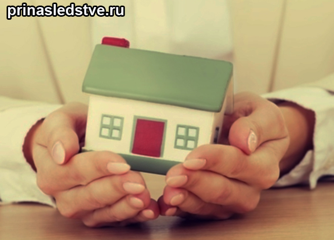 Человек держит в руках игрушечный домик
