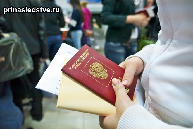 Человек держит свой паспорт и документы