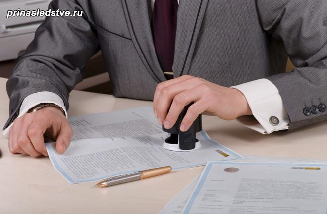 Нотариус ставит печать на документе