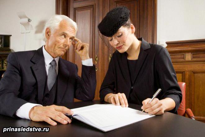 Мужчина в деловом костюме, дама в черном пишет бумагу