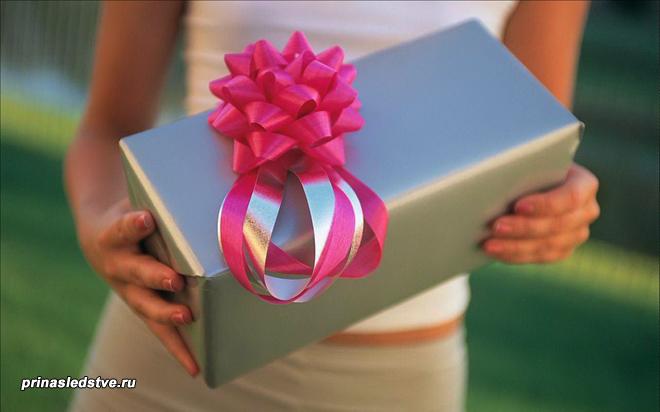 Девушка держит коробку с подарочным бантом