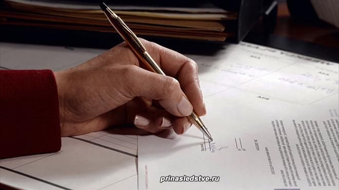 Мужчина расписывается в документах