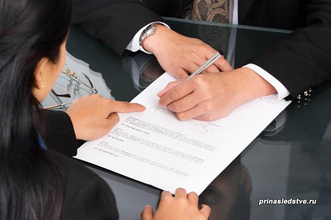 Девушка указывает место подписи мужчине в документе