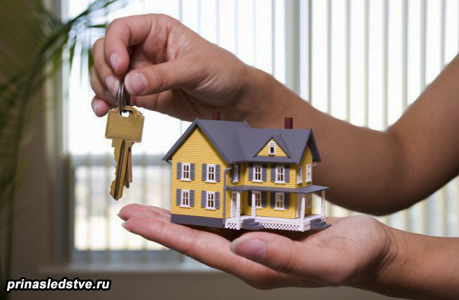 Мужчина держит ключи и макет дома