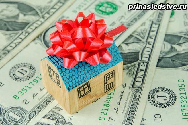 Маленький деревянный домик с подарочным бантом на денежных банкнотах