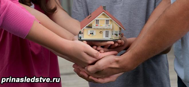Семья держит игрушечный домик