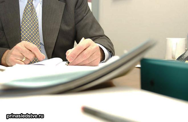 Мужчина в деловом костюме заполняет бумаги