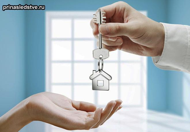 Передача ключей с брелком в виде домика из рук в руки