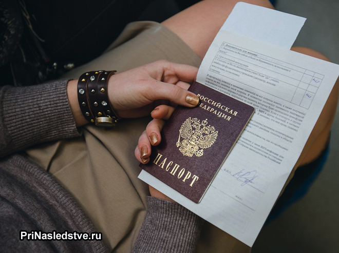 Мужчина держит паспорт в руке