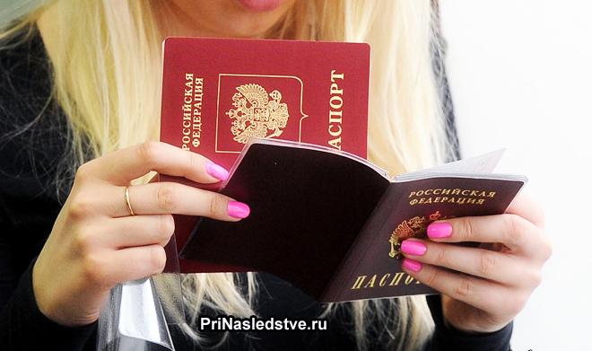 Блондинка держит в руках два паспорта