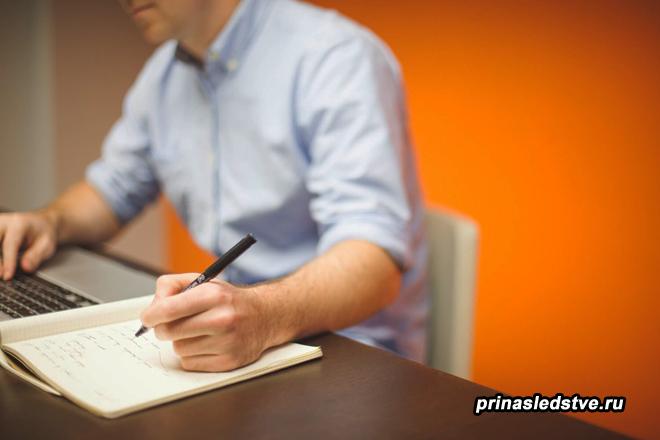 Мужчина за ноутбуком пишет на бумаге
