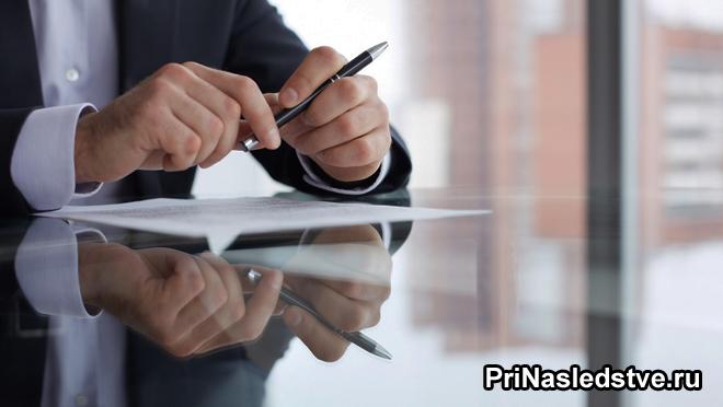 Мужчина в офисе подписывает документы