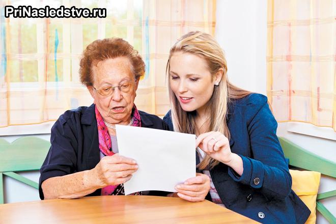 Женщина в возрасте изучает документы с юристом