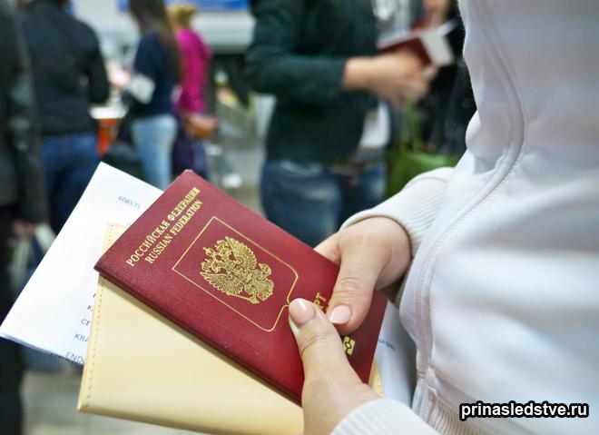 Девушка держит в руках паспорт и другие документы