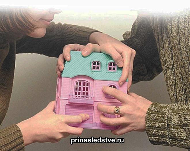 Девушка и мужчина делят игрушечный домик