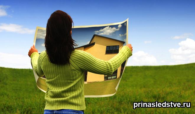 Девушка держит план будущего дома в поле