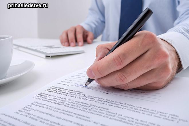 Человек в деловом костюме подписывает бумаги