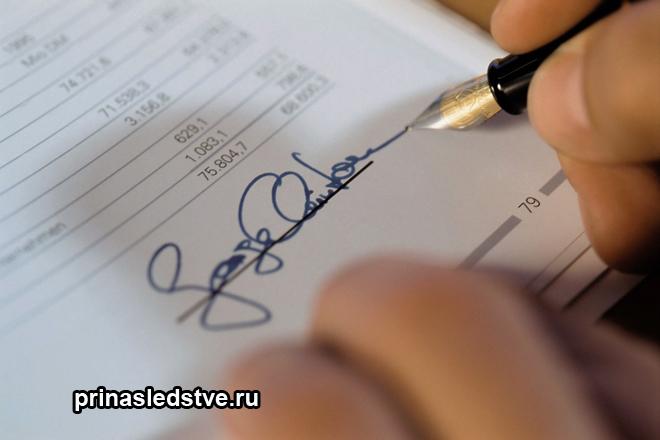 Человек ставит свою подпись