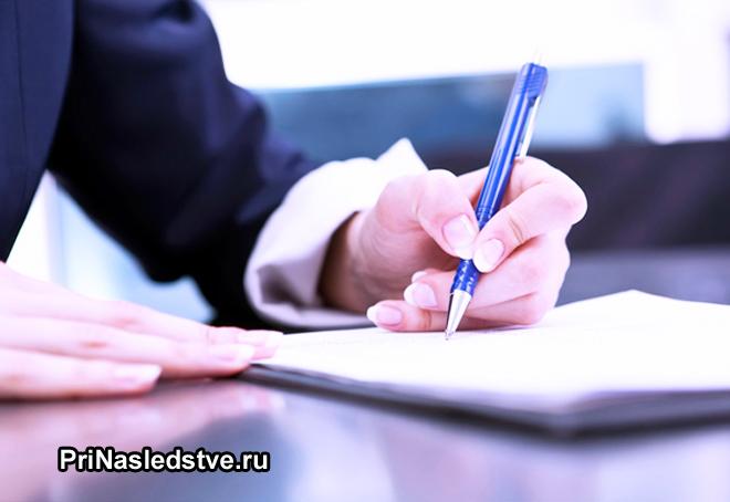 Мужчина в костюме пишет заявление на бумаге