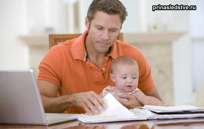 Папа сидит с ребенком и изучает бумаги