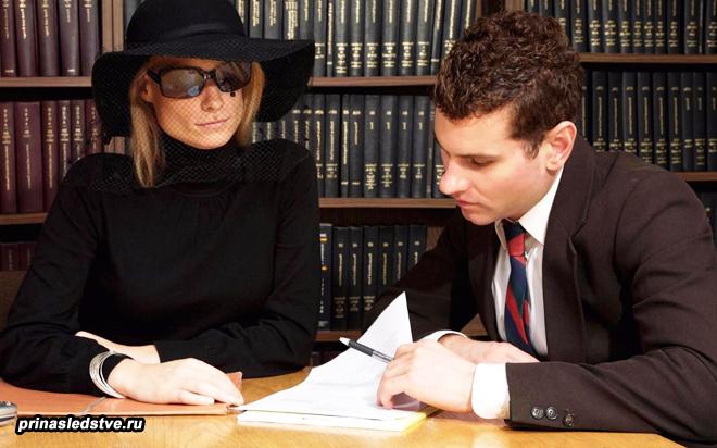 Девушка в черном подписывает документы у юриста