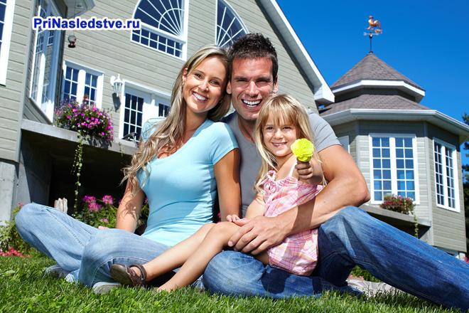 Счастливая семья сидит на лужайке перед домом