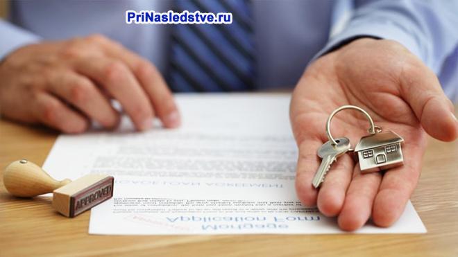 Мужчина держит в руке ключи от квартиры, рядом лежит договор