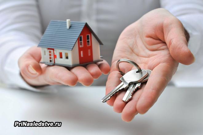 Мужчина держит в одной руке ключи, а в другой игрушечный домик