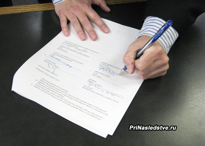 Мужчина ставит свою подпись в контракте