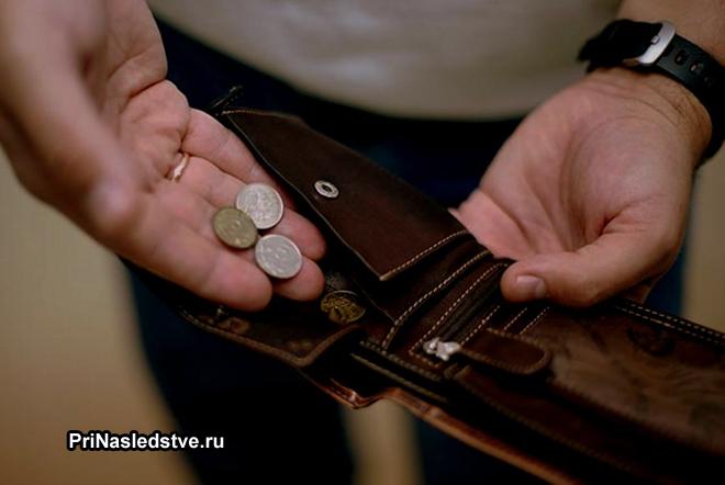 Мужчина достает монеты из кошелька