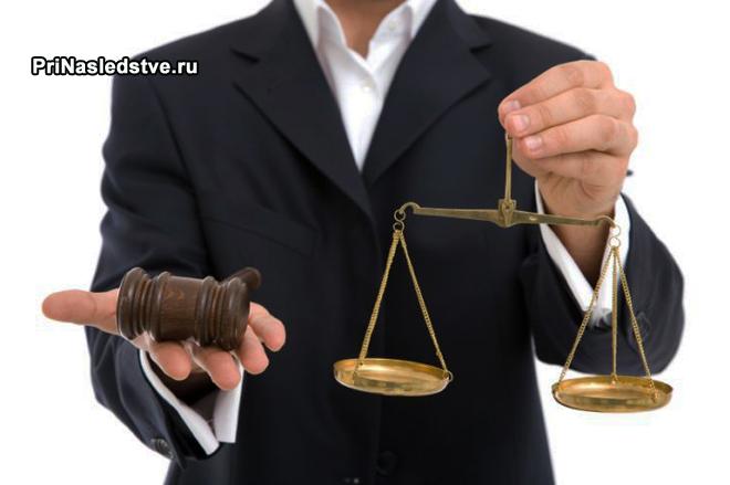 Бизнесмен держит в руках молоточек судьи, весы Фемиды