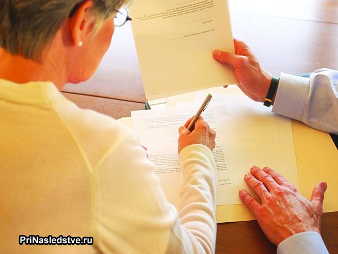 Женщина подписывает документы у нотариуса
