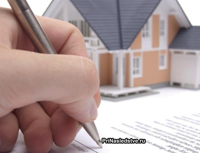 Девушка подписывает документ, игрушечный домик стоит на столе