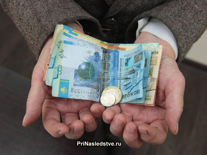 Мужчина держит в руках денежные купюры